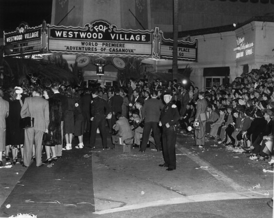 "A view of the premiere of the ""Adventures of Casanova"" at the Fox Westwood Village with an enormous crowd gathered in front of it"