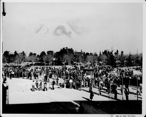 A crowd of people converges at a north entrance to the Coliseum in Los Angeles' Exposition Park