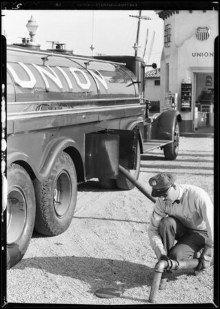 "New ""Leader"" banner and big truck at service station for bulletin cover, Southern California, 1932"