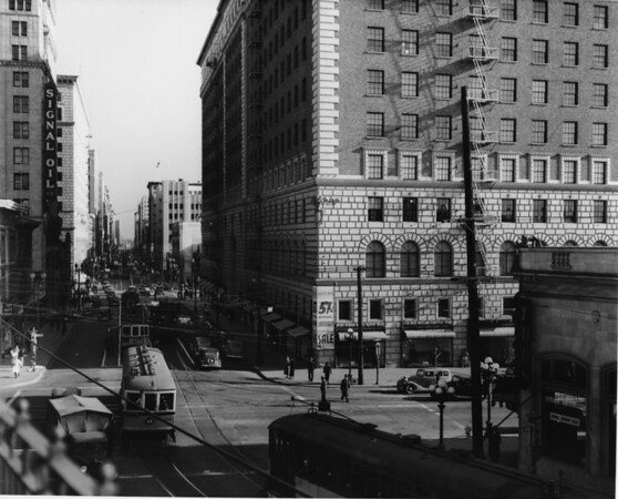 A view of Seventh Street and Figueroa Street, looking east along Seventh Street, showing the Signal Oil and Barker Brothers Buildings and the street crowded with cars and trolleys