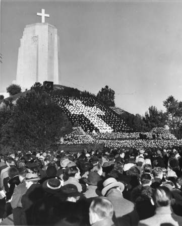 A huge cross stands in the background of a crowd of thousands during the Easter Sunrise Services at the Forest Lawn Memorial Park