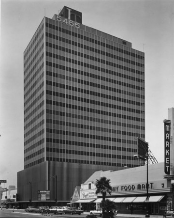 Photo of Lee Tower on Wilshire Boulevard, as well as a couple of food markets and Brown's Wilshire Bakery, facing west down Wilshire Boulevard