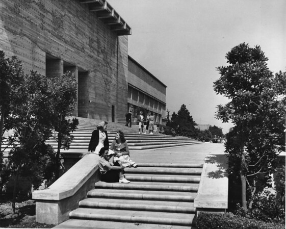 Students sitting on the steps of a school in front of the main library