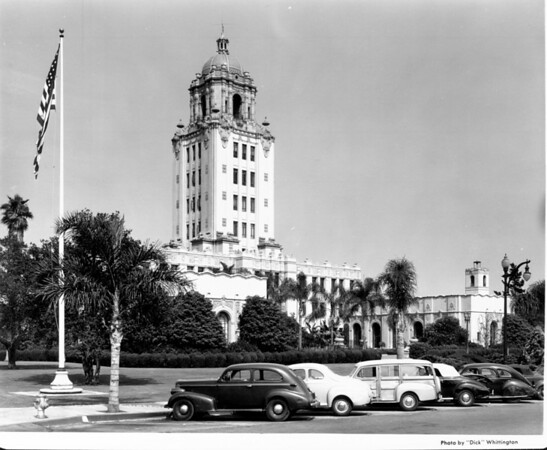 A corner view of the Beverly Hills City Hall with the American flag waving in the foreground