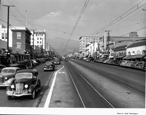 """Looking up Brand Boulevard in Glendale, CA, toward the mountains, past the Glendale theatre advertising Bing Crosby and Martha Raye in """"Waikiki Wedding"""""""