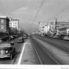 """Looking up a Glendale street toward the mountains, past the Glendale theatre advertising Bing Crosby and Martha Raye in """"Waikiki Wedding"""""""