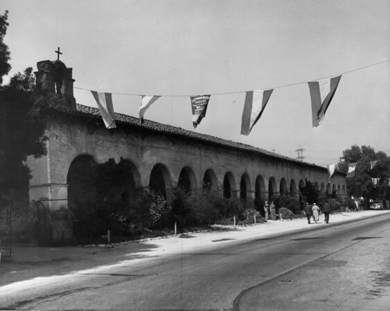 "A view of the San Fernando Mission showing a banner advertising the mission Pageant ""Prayer of the Padres"""