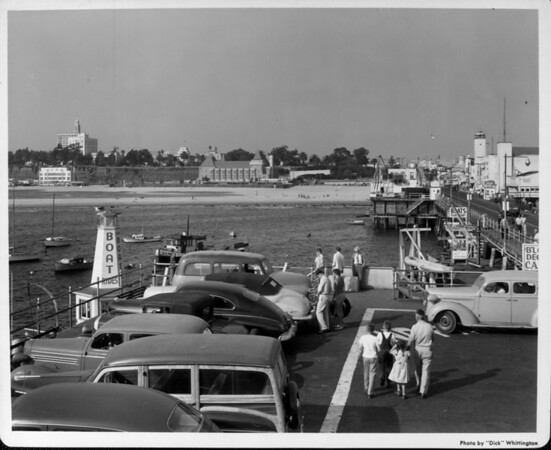 Cars parked and people walking along the Santa Monica Pier
