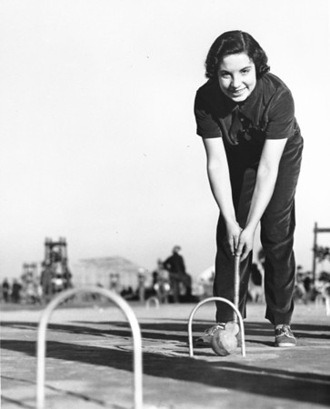 A woman poses for the camera as she prepares to stike a croquet ball in the middle of a Los Angeles playground