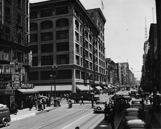 """In Downtown Los Angeles facing north on South Broadway at West Seventh Street Loew's State Theater (""""Songs, Love, Drama, Laffs""""), Milton's, Le Roy's, Kress, Fifth Street Store"""