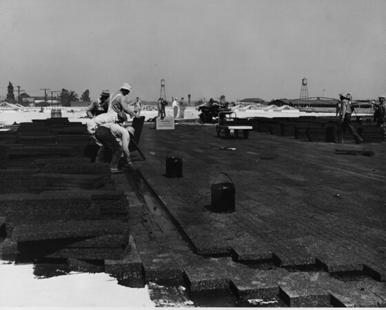 Building under construction, workers laying a rooftop