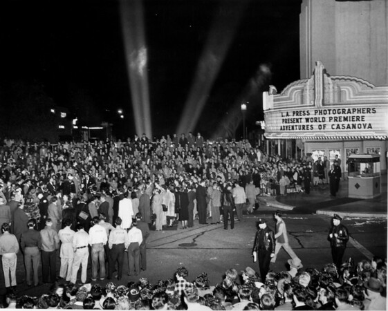 "Searchlights aim for the sky from behind some bleachers which seat the crowd in front of the Fox Westwood Village for the premiere of the ""Adventures of Casanova"""