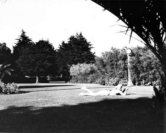 A woman laying in the grass in a park