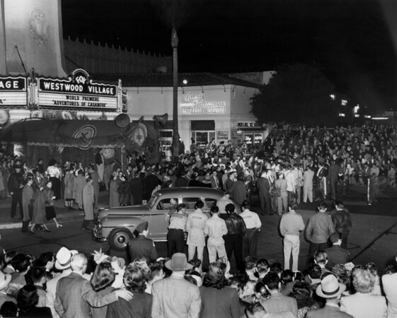 "A huge crowd looks at a fancy car as it pulls up to the Fox Westwood Village during the premiere of the ""Adventures of Casanova"""