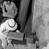 Workers rebuilding a wall at the San Fernando Mission with large adobe bricks