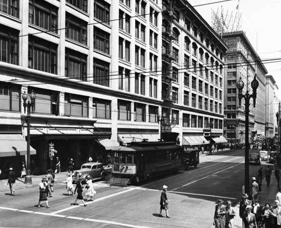 Seventh Street to the east of Hill Street, with a Los Angeles Railway streetcar bearing a Lucky Lager advertisement waiting for pedestrians to cross the street