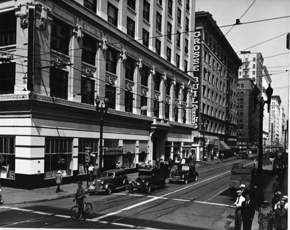 A row of buildings along Sixth Street and Main Street as people walk about the streets
