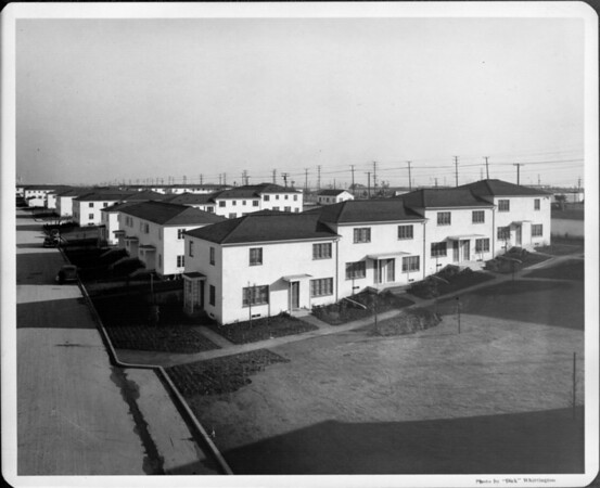 Housing complex with 2-story units divided by greenbelt and walkways