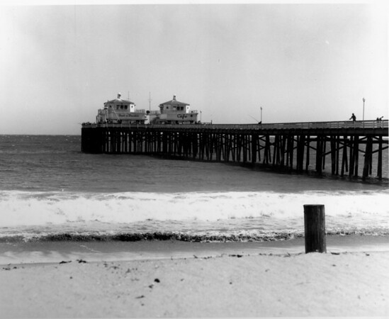 A view of two restaurants on the pier of Malibu beach as waves roll onto the sand