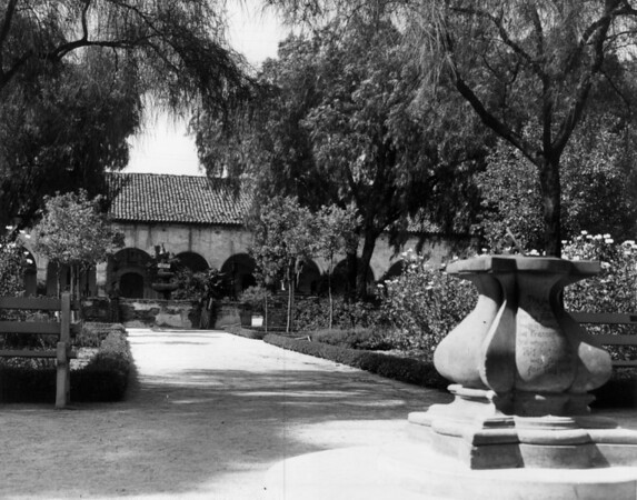 Two women in historical costumes stand in front of a fountain in the San Fernando Mission