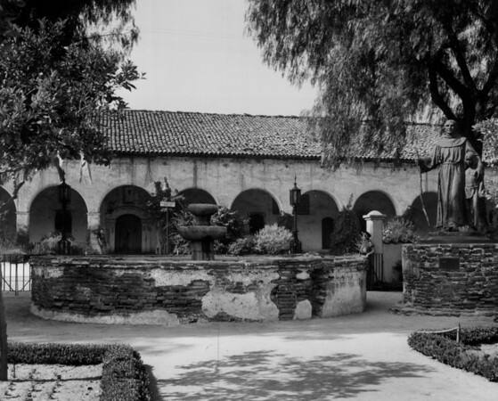 Two women in historical costumes stand in a courtyard of the San Fernando Mission