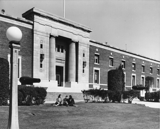 A school building as students sit on the front lawn