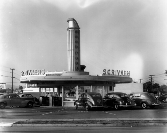 A view of Scrivner's Restaurant which is a circular building cars parked around it