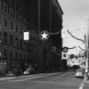 Seventh Street decorated for Christmas, looking west from the corner of Seventh Street and Flower Street, showing Signal Oil, Studebaker, and Pig 'n' Whistle Cafe signs