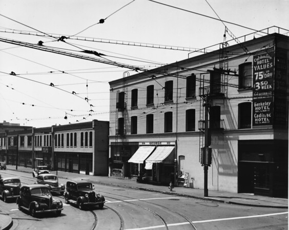 From the corner of Ninth Street and Main Street, cars and trolley car wires are seen