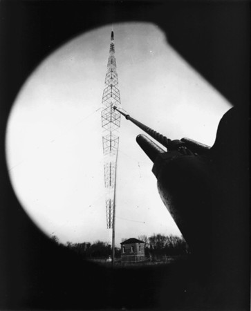 Outdoor photo of a large radio tower and equipment, outside of a radio station