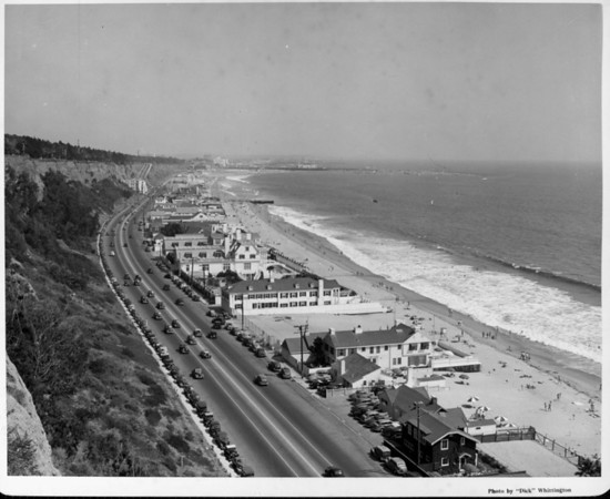 An high-angle view of the Santa Monica coastline crowded with houses, cars, and people on the beach