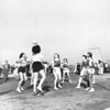 A group of women compete in a game of volleyball as many other people look on