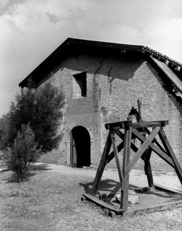 A wooden frame holding a bell standing in front of a building at the San Fernando Mission