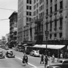 A Traffic Officer guides the traffic at the corner of South Spring Street and Fifth Street as cars and pedestrians crowd the streets