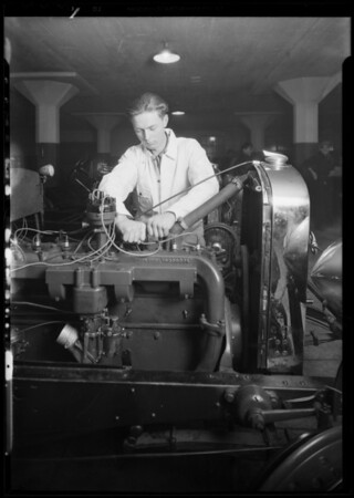 Men working on motor of car, National Auto School, Southern California, 1930