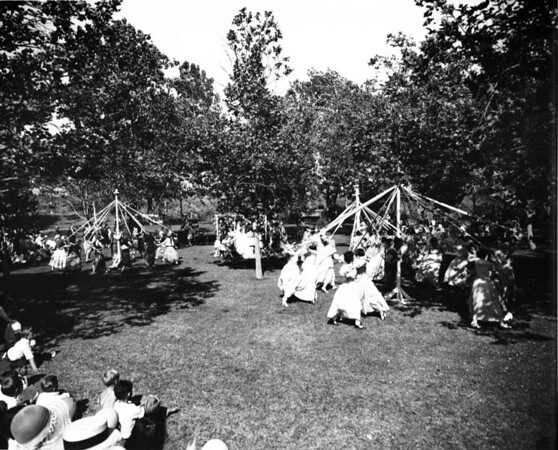 A bunch of people perform a ceremony at one of Los Angeles' many parks, as many citizens watch the performance
