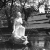 A sculpture of a mother and a child in a fountain at the Forest Lawn Memorial Park