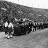 Shrine parade at Coliseum featuring two African American men pulling float, followed by Shriners in procession