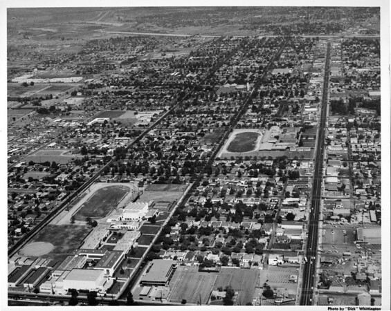 Aerial view of a commercial district and a residential district including two educational institutions with tracks