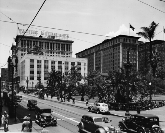 A shot of the Pacific Mutual Building with the morning streets crowded with people and cars