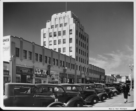 A lady looking at a row of cars in front of the Central Tower Building in Santa Monica