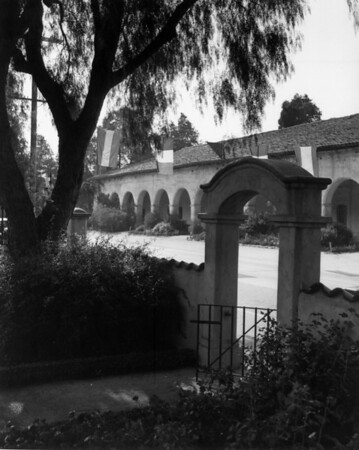 A view of the San Fernando Mission showing a gate and flags and banners for the mission's pageant