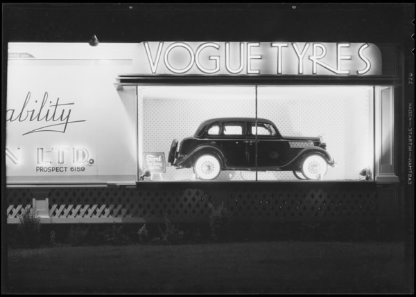 Vogue Tyre sign board with Ford sedan, Southern California, 1935