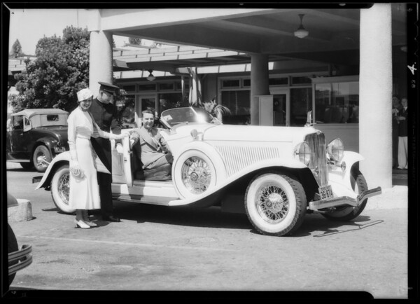 Lita Ray and Cliff Henderson putting Air Races stickers on car, Southern California, 1933