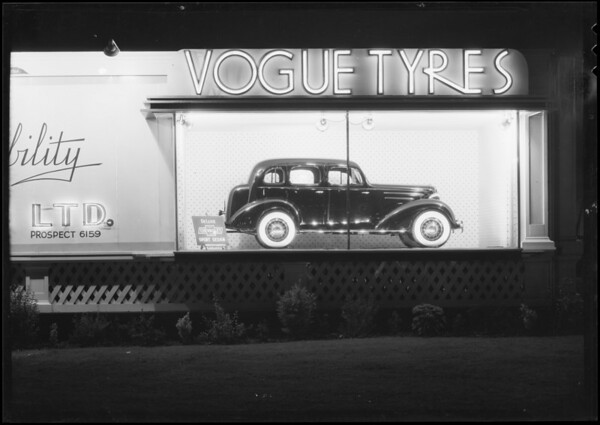 Vogue Tyre board with Chevrolet sedan, Southern California, 1935