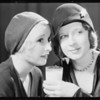 Two girls talking at table & glass of milk, Fresh Milk Industries, Southern California, 1931