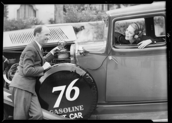 Earl Cooper and microphone on motor of car, Southern California, 1932