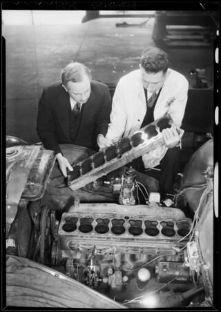 Examining motor of 60,000 mile Studebaker, Southern California, 1934