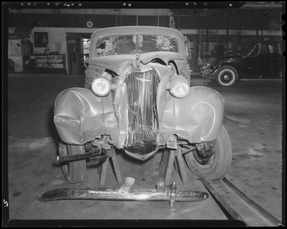 Wrecked 1937 Chevrolet sedan and 1938 Ford sedan and intersection of Winona Avenue and North Ontario Street, Southern California, 1940