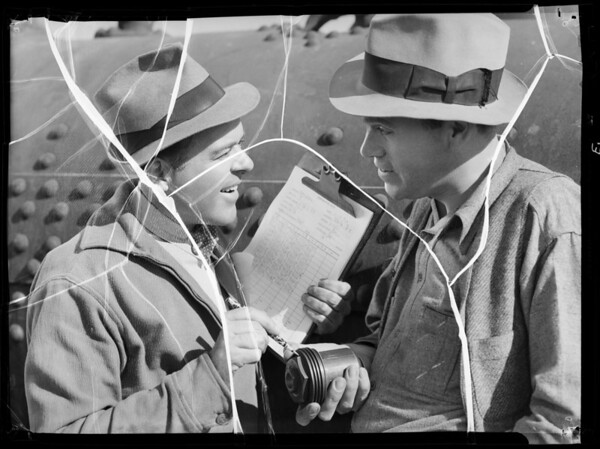 Truck driver and driller discussing shooting well, Southern California, 1936